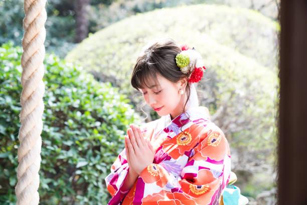 Attractive asian woman wearing japanese kimono praying at a Shinto shrine. stock photo