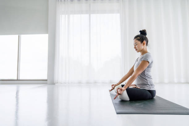 Attractive asian women do Yoga exercises at home stock photo
