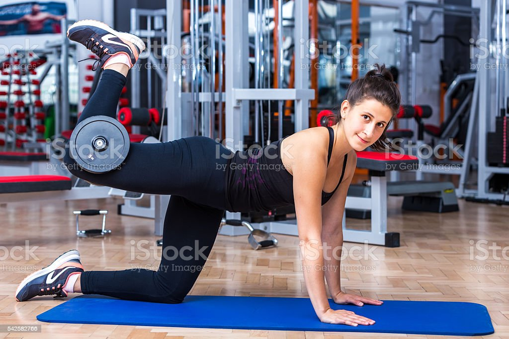 Attractive, athlete girl while performing the glute kickback exe stock photo
