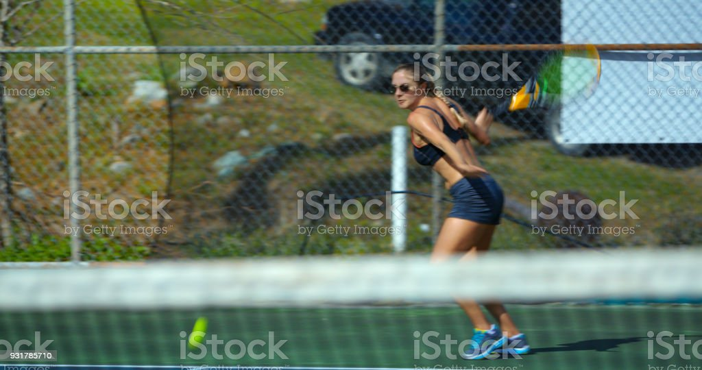 attractive athletic woman playing tennis in the tropics stock photo
