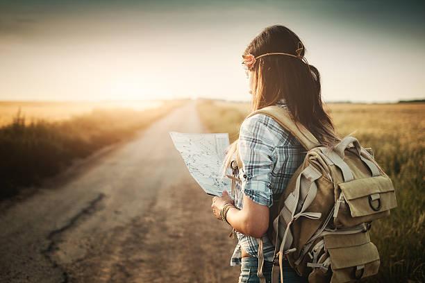 atractiva joven mirando el mapa mochilero - mochilero fotografías e imágenes de stock