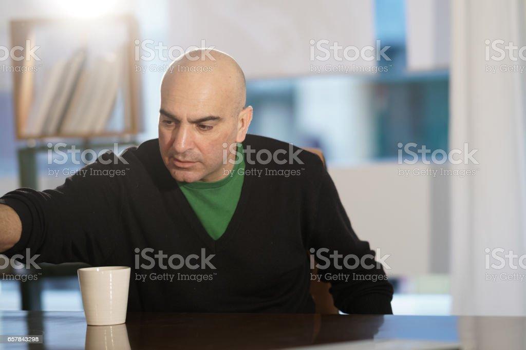 Attractive bald headed office worker at desk