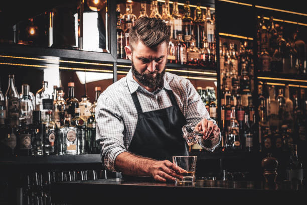 Attractive barmen is prepairing drinks Diligent serious barman is preparing alcoholic beverege for customer. bartender stock pictures, royalty-free photos & images