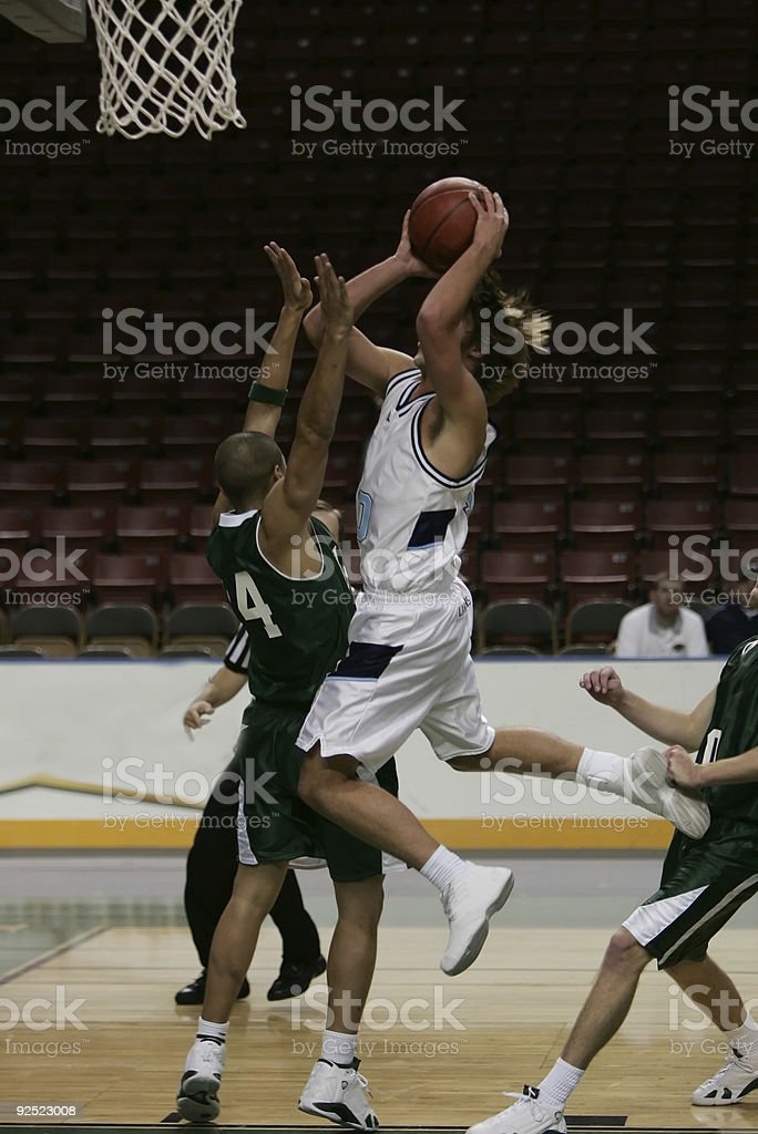 Attractive Basketball Player in White Charges His Way to Basket royalty-free stock photo