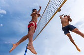 Bottom view of volleybal players in the attractive action on the net