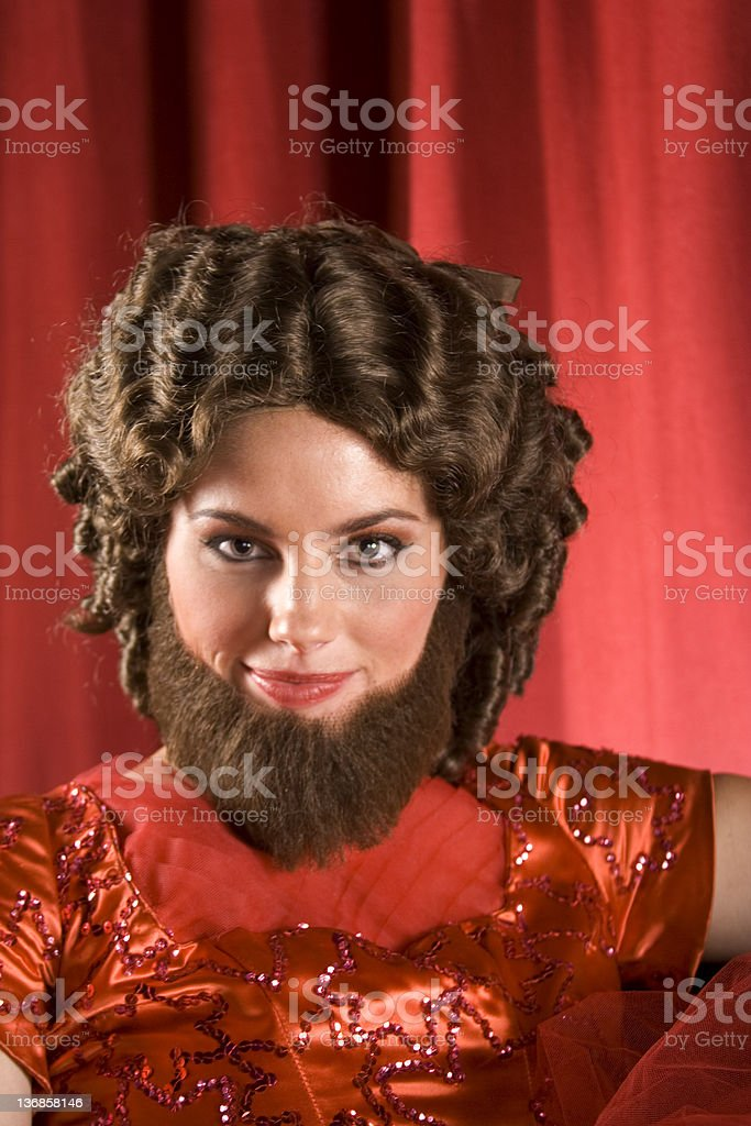 Attractive Bearded Lady In Red An attractive young bearded lady smiles coyly at the camera. 20-24 Years Stock Photo