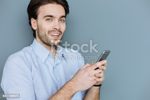 Digital native. Attractive positive bearded man holding his smartphone and smiling to you while chatting online