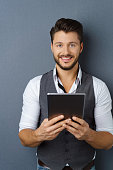 Attractive bearded man holding a tablet pc
