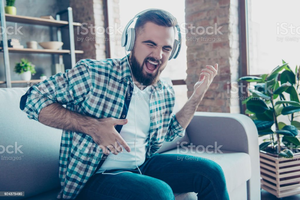 Attractive, bearded man sitting on the couch in living room, having headphones on his head, listening his favorite music, singing a song dreaming like playing guitar stock photo