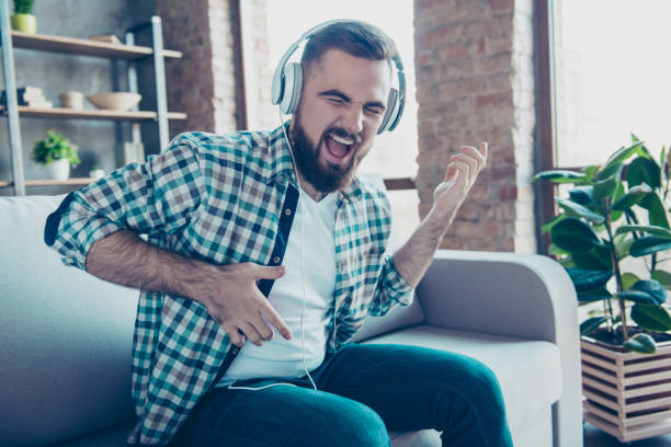 attractive, bearded man sitting on the couch in living room, having headphones on his head, listening his favorite music, singing a song dreaming like playing guitar - rock music stock pictures, royalty-free photos & images
