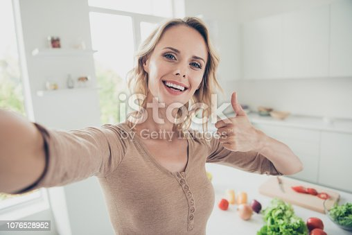 Attractive beautiful gorgeous lady in casual outfit with her blond curly wavy hair she demonstration thumbs up make white smile stand inside cozy comfort apartment make selfie
