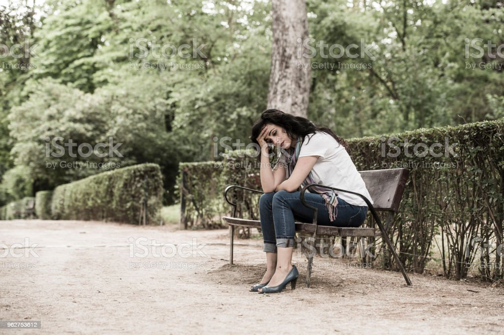 attractive beautiful latin woman sitting on a park bench feeling sad and depressed in a park outside in europe - Foto stock royalty-free di Abbigliamento casual