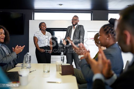 Group of mixed race colleagues in modern meeting room with laptop computer encouraging two attractive African American business professionals leading a collaborative discussion