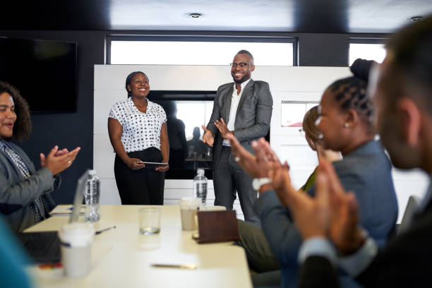 Attractive black businessman being encouraged by diverse multi-ethnic group of coworkers during presentation in office Group of mixed race colleagues in modern meeting room with laptop computer encouraging two attractive African American business professionals leading a collaborative discussion african american ethnicity stock pictures, royalty-free photos & images