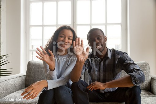 Black African cheerful married couple sitting on coach at home. Wife and husband have video call using computer, waving their hands greeting or saying goodbye to friends and smiling looking at camera