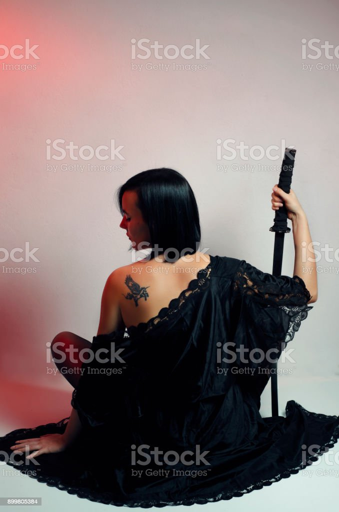 Attractive black hair mystic woman with tattoo and samurai sword,...
