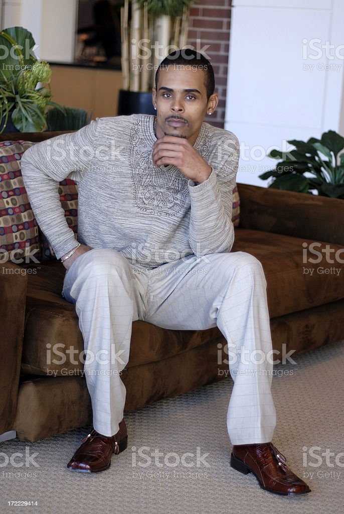 Attractive black male model sitting on couch royalty-free stock photo