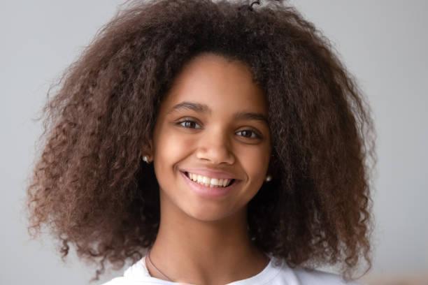魅力的な黒ティーンエイジャー女の子笑顔見てカメラ - gen z ストックフォトと画像