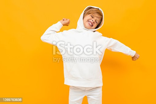attractive blond boy in a white hoodie screaming out loud on an orange wall.