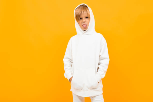 attractive blond boy in a white sweater with a hood on an orange background with copy space stock photo