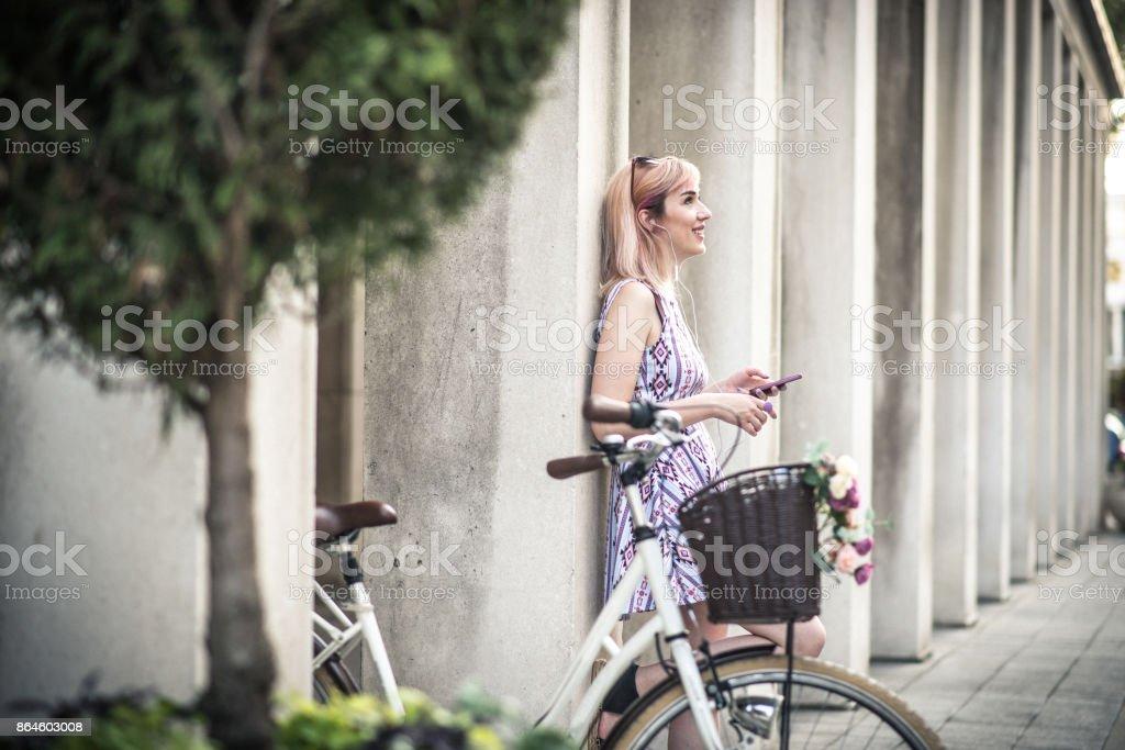 Attraktive blonde Frau, die gerne mit dem Fahrrad zur Arbeit gehen Lizenzfreies stock-foto