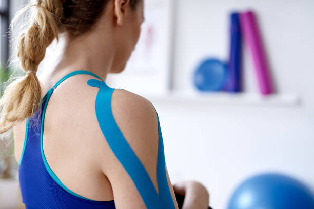 attractive blond woman in a bright sport therapy office with kinesio tape on her neck and shoulder to heal pain - sports medicine stock pictures, royalty-free photos & images