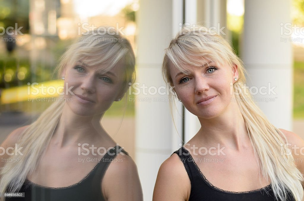 Attractive blond woman reflected in a glass window stock photo