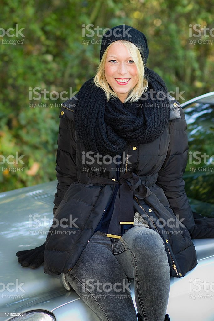 Attractive blond woman sitting on her car motorhood royalty-free stock photo