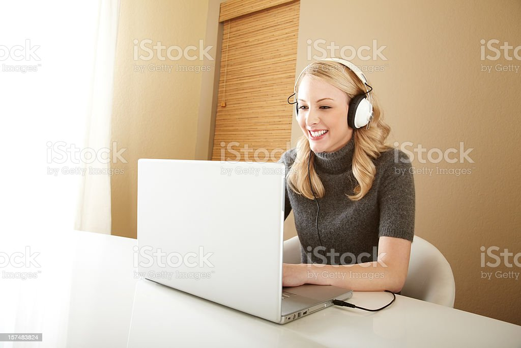 Attractive Blond Woman Smiling and Listening to Music on Laptop Smiling young woman listening to music on the laptop with headphones at home 20-24 Years Stock Photo