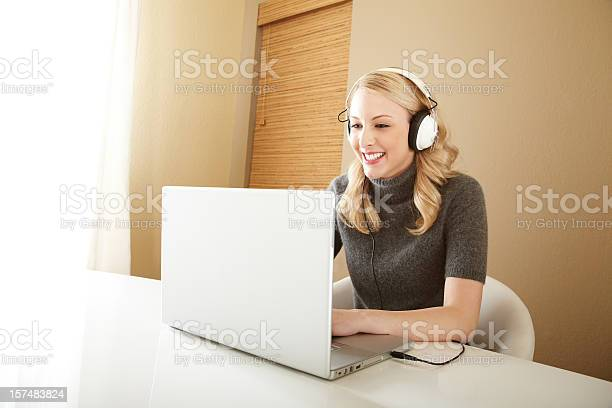 Attractive Blond Woman Smiling And Listening To Music On Laptop Stock Photo - Download Image Now