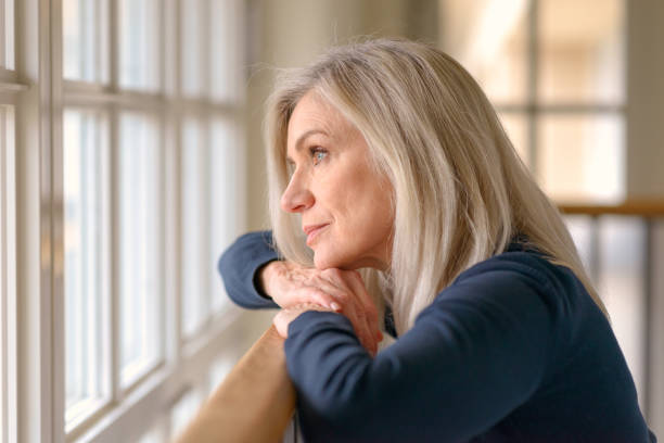 Attractive blond woman standing daydreaming stock photo