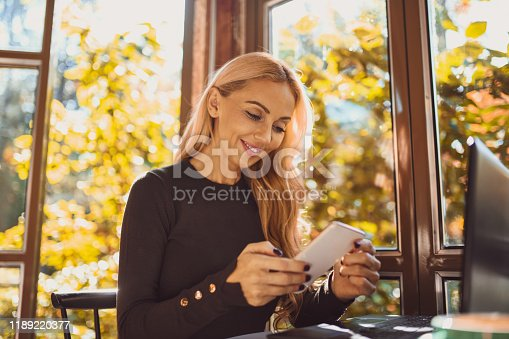 Attractive blond caucasian woman chatting on her smart-phone with laptop in front of her. She's smiling, sitting by the window inside a cafe. There are trees and plants outside.