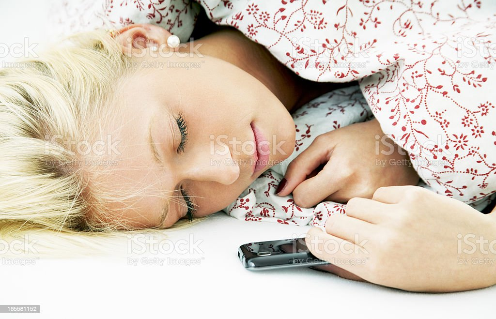 Attractive blond young sleeping woman in bed with smartphone royalty-free stock photo