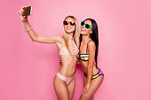 Attractive, blonde, brunette, seductive, pretty, charming, joyful, fit, stylish, cheerful, trendy tourists, ladies in swim suits shooting self portrait on smart phone, posing over pink background