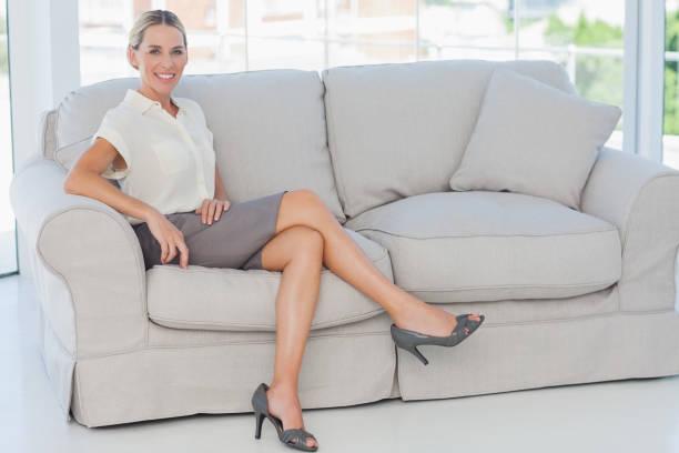 attraktive blonde geschäftsfrau posieren sitzt auf sofa - damenschuhe 44 stock-fotos und bilder