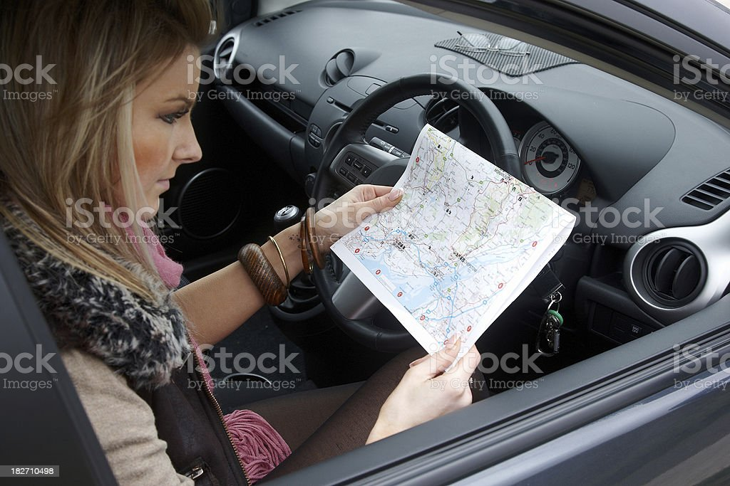 Attractive blonde female car driver looking at map royalty-free stock photo