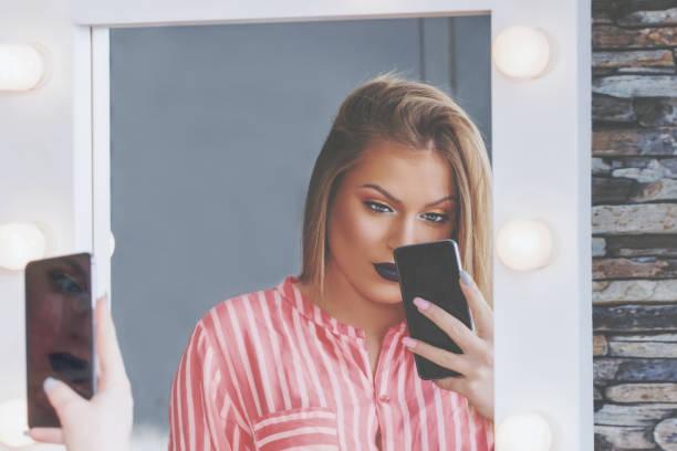 Attraktive Blondine macht Selfie in Make-up-Spiegel mit Lampen – Foto