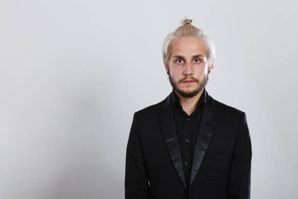Attractive blonde man in bun Male hairstyle, elegant fashion concept. Attractive blonde man having hair bun wearing black shirt and jacket looking straight to camera man bun stock pictures, royalty-free photos & images