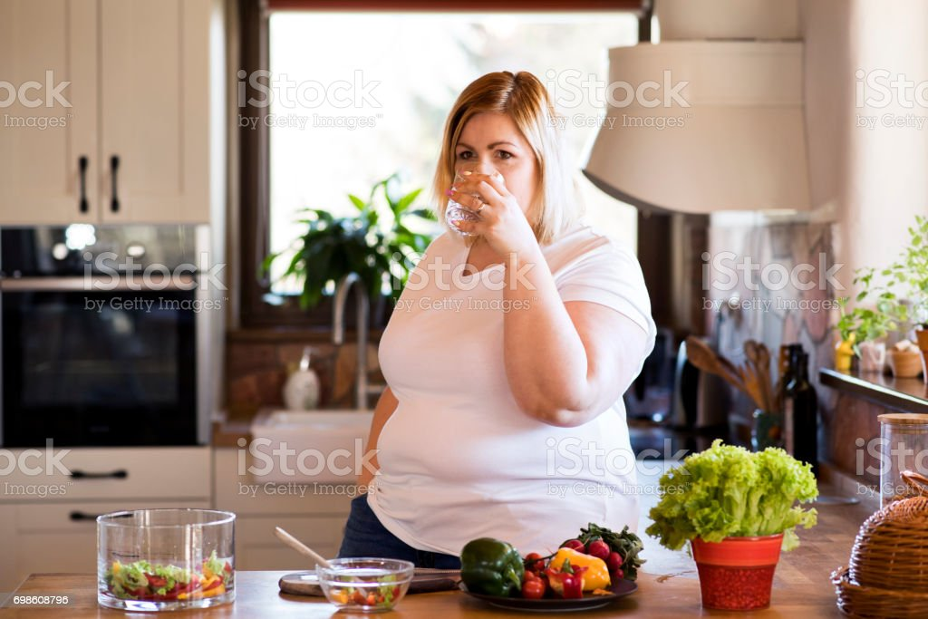 Attractive blonde overweight woman in white t-shirt at home preparing healthy vegetable salad in her kitchen, drinking water. stock photo