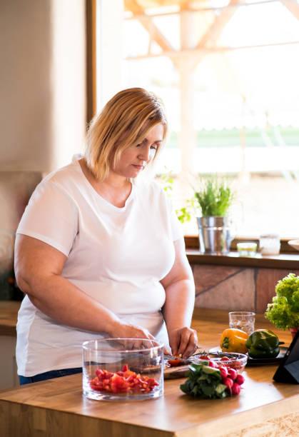 attraktive blonde übergewichtige frau in weißem t-shirt zu hause bereitet einen leckeren gesunden salat gemüse in ihrer küche. - backofenfenster reinigen stock-fotos und bilder