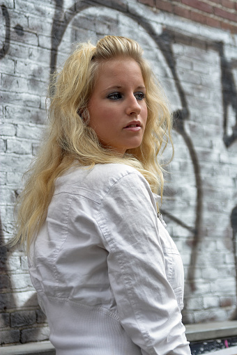Attractive Blonde Standing Against Graffiti Stock Photo - Download Image Now