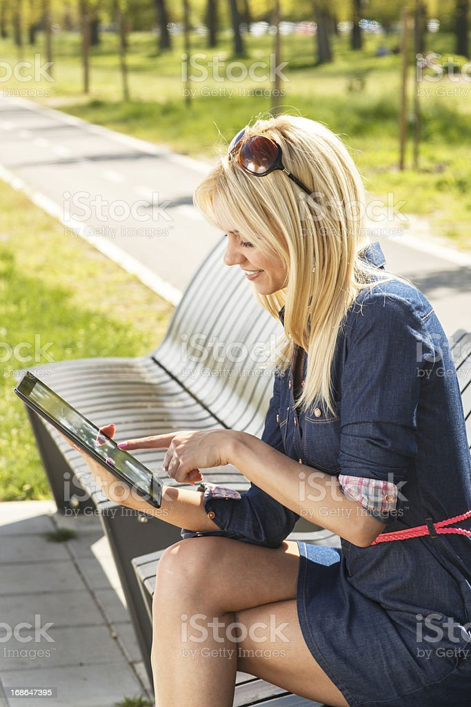 Attractive blonde using digital tablet royalty-free stock photo