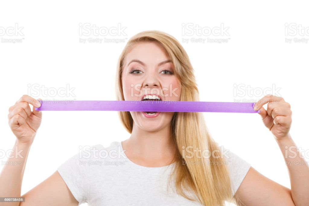 Attractive blonde woman biting tape on mouth. stock photo