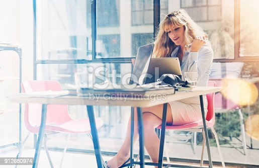 istock Attractive blonde woman working at the modern office loft.Coworker using electronic touch tablet computer on workplace.Horizontal. Blurred background. 912680974