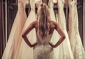 Back view of attractive young bride choosing wedding dress in modern wedding salon