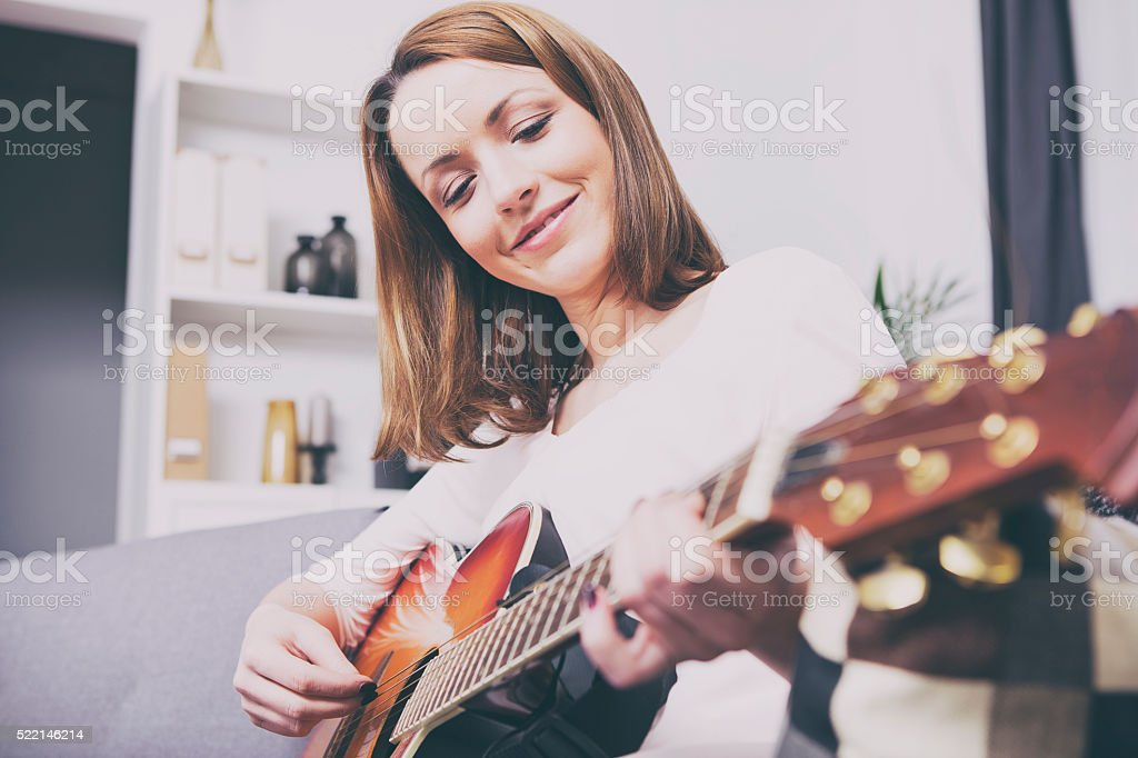 Attractive brown haired girl sitting smiling on couch stock photo