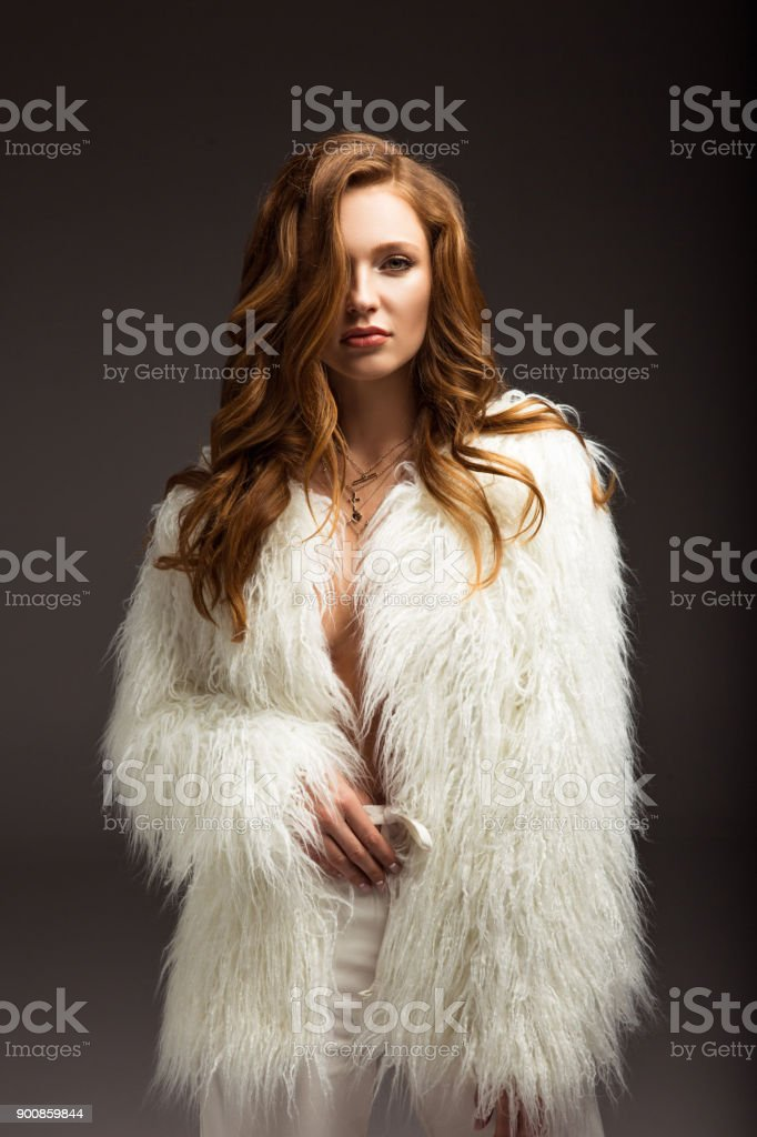 attractive brown-haired woman in fluffy jacket isolated on gray stock photo