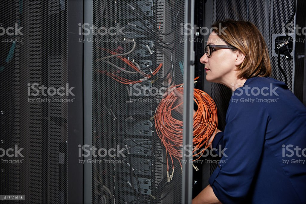 Attractive brunette adult female employee working in internet server room stock photo