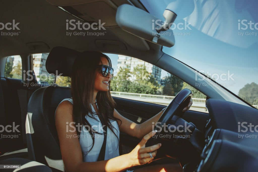 Attractive brunette drives a car stock photo