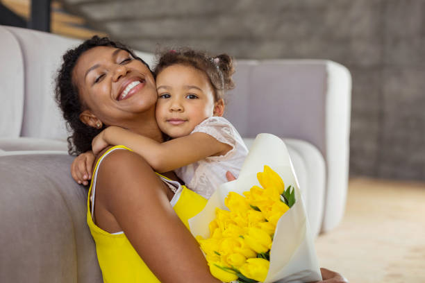attractive brunette girl caressing her young mother - mothers day stock pictures, royalty-free photos & images